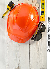 hardhat and safety glasses on wooden background