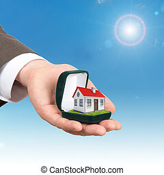 Empty ring box with house in man hand