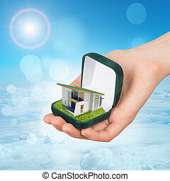Empty green ring box with house in humans hand