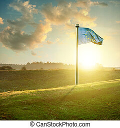european union flag on sunset landscape with green field and...