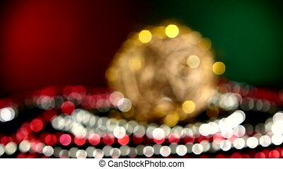 Unusual gold toy for Christmas or New Year and beads, rotation, on red and green, bokeh, dynamic change of focus