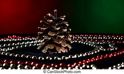 Pine cone for Christmas or New Year and beads, rotation, on red and green