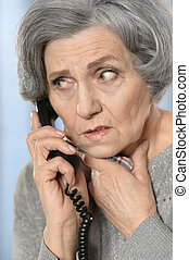 Senior woman calling her doctor - Portrait of a sick senior...