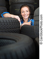 Young woman surrounded by car tyres - Young, pretty,...