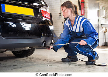 Mechanic, checking diesel exhaust emission rates - Female...