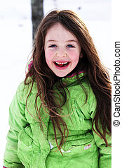 Winter Joy - a young girl enjoying playing outside in the...