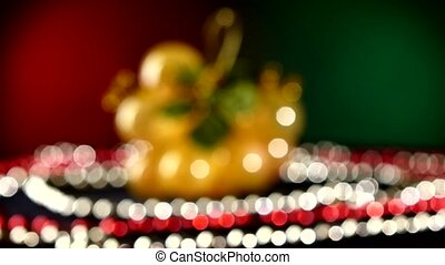 Toy like grapes for Christmas or New Year and beads, rotation, on red and green, bokeh, dynamic change of focus