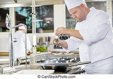 Chef adding pepper on steak in a professional kitchen - Chef...