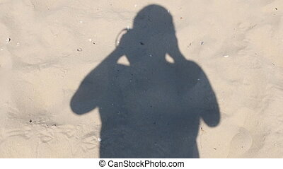Man walking on the beach and takes off his shadow HD