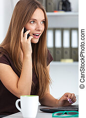 Portrait of surprised business woman talking on phone -...