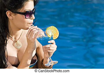 Stunningly beautiful young latina Hispanic woman drinking a cocktail by a blue swimming pool
