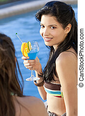 Stunningly beautiful young latina Hispanic woman in drinking a cocktail by a blue swimming pool with her friend in the foreground.