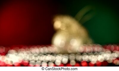 Shiny unusual gold toy for Christmas or New Year and beads, rotation, on red and green, bokeh, dynamic change of focus