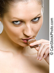 Sexy girl eating chocolate, closeup picture over grey...