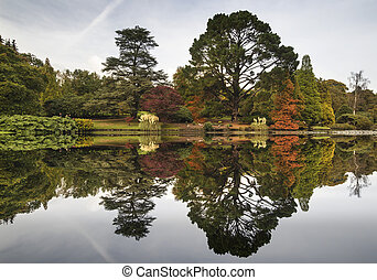 Beautiful Autumn Fall forest landscape reflected in calm lake