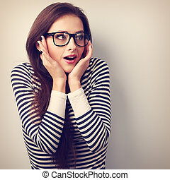 Fun surprising young woman in eyeglasses looking on empty copy space background