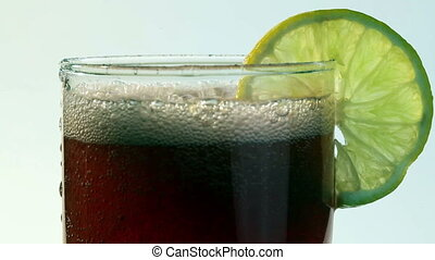 Red Carbonated Drink Poured Into Glass With Lemon Closeup