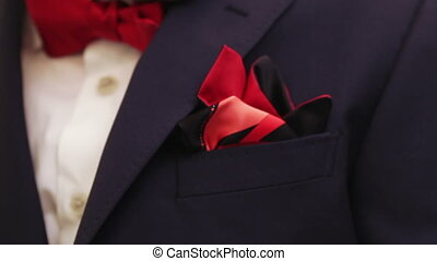 Groom corrects scarf - Young male adjusts his red...
