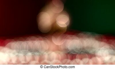 Unusual candy toy for Christmas or New Year and beads, rotation, on red and green, bokeh, dynamic change of focus