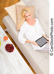 Woman with tablet and cherry on the sofa - A mature woman...