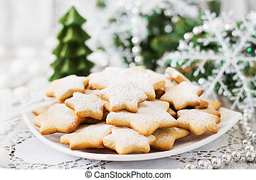 Christmas cookies and tinsel on a light wooden background.