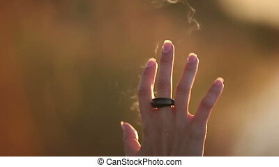 Female Hands Touching Light Beams and Smoke Trails during...