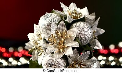 Unusual flower toy for Christmas or New Year and beads, rotation, on red and green, close up