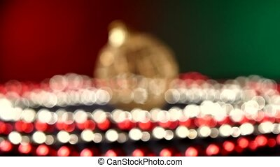Unusual round toy for Christmas or New Year and beads, rotation, on red and green, bokeh, dynamic change of focus