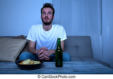 Young man watching a sad movie at night with chips and beer...