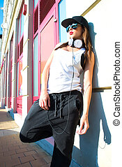 Rapper girl with headphones in a european city - A beautiful...