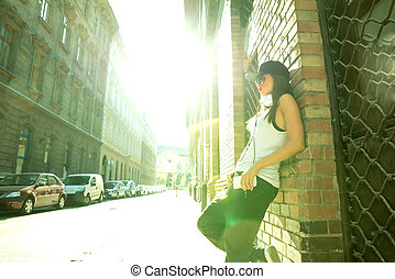 Hip hop girl with headphones in a urban environment - A...