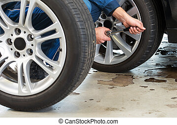 Mechanic changing tires - A mechanic tightening the wheel...