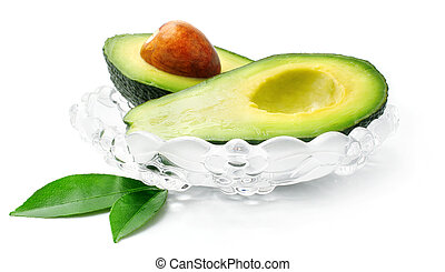 fresh avocado fruit with green leaves in glass dish