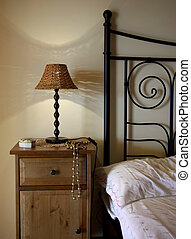 Bedside - Detail of bed and bedside table with lamp.