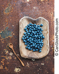 Blueberries in a rustic wooden serving dish over grunge metal rusty background, top view.