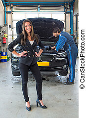 Sales woman standing in front of a car, being serviced for delivery by a mechanic