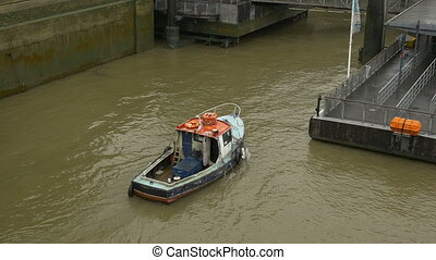 Boat on Muddy Waters - Above view of a motorized boat slowly...