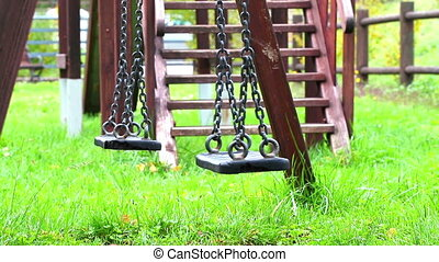 empty swings swaying at playground for child, moved from...