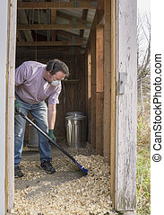Chicken Farmer Cleaning A Coop Out - Chicken farmer cleaning...