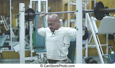 bodybuilder exercising pectoral at gym.
