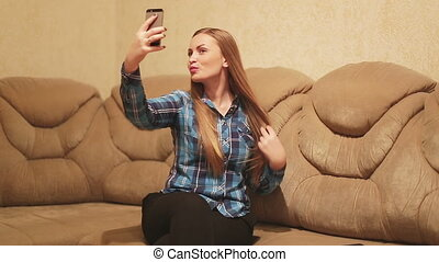 Young woman taking a self-portrait with her smartphone