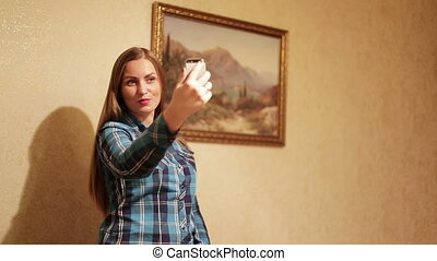 Young woman taking a self-portrait with her smartphone.