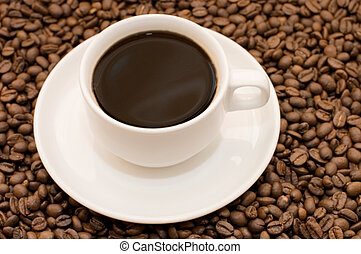 White coffee cup filled with coffee beans