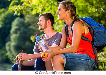 Couple hiking in summer drinking water