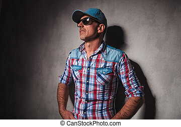 pensive mature casual man with hands in pockets wearing a...