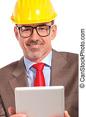portrait of a smiling construction engineer holding tablet...