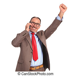 happy old businessman winning on the phone, standing with...