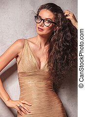 brunette wearing glasses poses while fixing her hair -...
