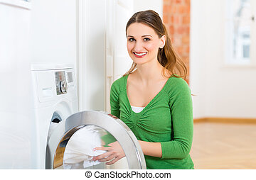 Housekeeper with washing machine - Young woman or...