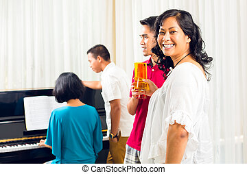 Asian people sitting together at the piano and having fun...